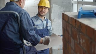 Tilt up of cheerful Asian construction worker in hard hat and overalls discussing blueprint with male colleague
