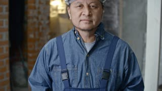Tilt up of cheerful mature Asian builder in hard hat and overalls standing in unfinished building and smiling for camera