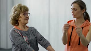 Medium shot of female fitness trainer helping elderly woman doing curls exercise with light dumbbells