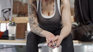 Handheld camera shot of sweaty tattooed woman sitting on bench in gym, looking at her hands and heavily breathing after intensive workout
