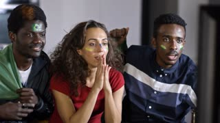 Woman and two African-American friends sitting on couch with flag and cheering on Brazil team, yelling, getting joyous and embracing while watching soccer on TV at home