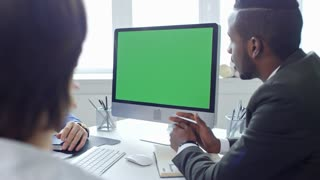Young african american businessman discussing ideas with colleagues at meeting in the office and having web conference on computer with chroma key screen