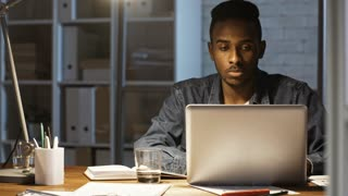 Young african american businessman sitting at desk in the office at night, typing on laptop and writing down in notepad