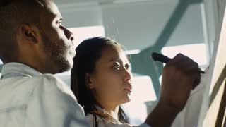 Young african american man and asian woman writing on flipchart and discussing business plans in the office at sunny day