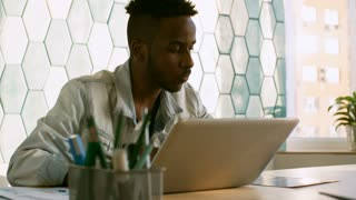 Young african american man sitting at table in office and typing on laptop while working on business project