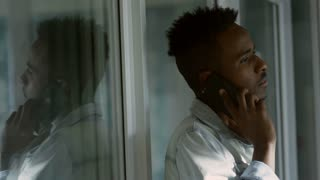 Young African American office worker standing by the glass wall in office and speaking on mobile phone