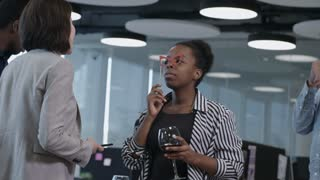 Young African business lady holding paper eyeglasses on stick and posing at camera with glass of wine while female colleague photographing her with smartphone at corporate party