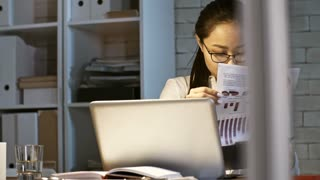 Young asian business lady in eyeglasses analyzing financial documents and using computer while working late in the office