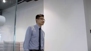 Young Asian businessman walking into office, shaking hands with African colleague, smiling and walking to workplace
