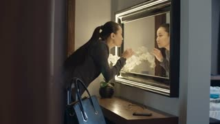 Young Asian businesswoman fixing make up in front of the mirror in hotel apartment, taking her eyeglasses and walking away