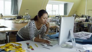 Young Asian fashion designer leaning on table and using desktop computer when working at tailoring shop