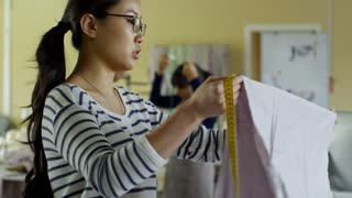 Young Asian fashion designer showing piece of pastel colored fabric to client and discussing project with them