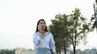 Young Asian lady walking on street in the city at summer day and talking on mobile phone