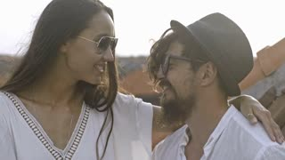 Young Asian man in sunglasses and hat sitting with girlfriend on rooftop at romantic date on vacation. Loving couple embracing, taking and smiling