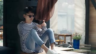 Young Asian man in sunglasses sitting on outdoor terrace in summer cafe and typing on smartphone