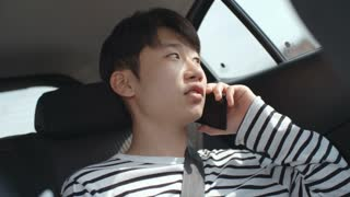 Young Asian man riding in backseat in car and speaking on mobile phone