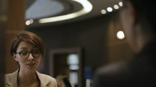 Young attractive businesswoman in eyeglasses smiling and talking with receptionist at front desk in hotel