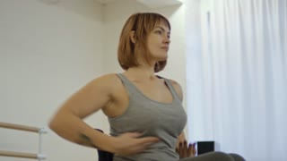 Young attractive woman in wheelchair moving arms while learning dance in studio