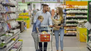 Young beautiful family walking in supermarket: man pushing shopping cart with his little son and woman carrying paper bag with groceries