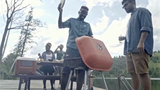 Young black man cooking meat for picnic by lake and using plastic plate to blow extra air in the grill, his friends relaxing in the background