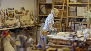 Young blonde woman using sanding machine on wooden plank when doing diy project in carpentry workshop