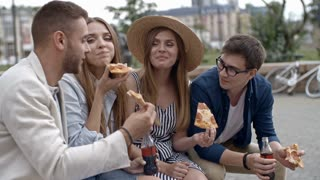 Young couples drinking coke from glass bottles, eating pizza, talking and laughing while sitting on bench outdoors