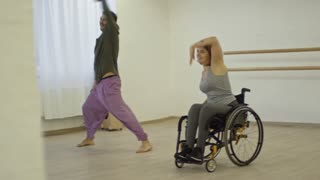 Young disabled woman in wheelchair smiling and laughing while learning energetic dance with male partner in studio