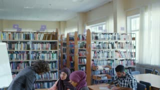 Young female teacher walking in classroom and helping adult middle eastern students while giving English lesson in public library