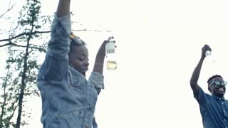 Young friends of different ethnicities drinking and dancing with their hands in the air at party outdoors
