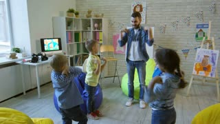 Young male teacher talking and doing shoulder exercises with group of little cute kids in kindergarten classroom