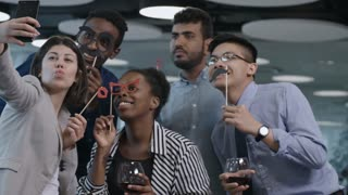 Young multi-ethnic team of business men and women holding funny mustache and eyeglasses on sticks, smiling and grimacing at camera of smartphone while taking picture at office party