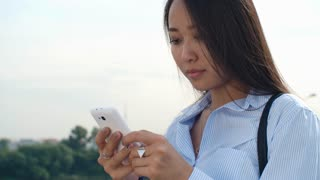 Young pretty woman of Asian ethnicity standing outdoors at summer day and typing on modern smart phone
