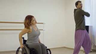 Young smiling woman in wheelchair enjoying energetic dance with male partner in studio