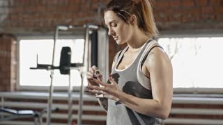 Young sweaty woman with tattooed body wrapping her fingers with tape and cutting it with teeth while training hard in gym