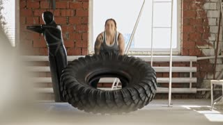 Young tattooed woman having cross training workout with heavy tire in gym