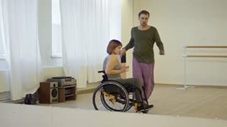 Young woman with paralyzed legs dancing in wheelchair with male choreographer in studio