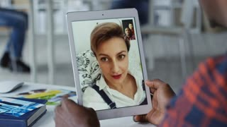 Young woman with short haircut having video call with her two friends, one of them is holding tablet computer and waving hand to her