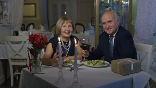 Zoom in of cheerful senior couple holding glasses with wine and looking at camera while having romantic date in restaurant