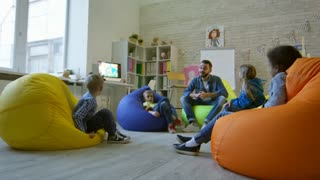 Zoom in of group of little kids sitting on colorful bean bags chairs around male teacher and listening to him while taking a lesson in kindergarten classroom