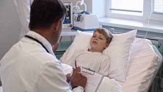 Zoom in of little boy lying on hospital bed and talking to doctor while nurse monitoring his pulse with medical equipment
