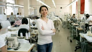 Zoom in of middle-aged Asian woman standing in sewing factory, looking at camera and smiling while seamstresses working with textile in background