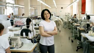 Zoom in of middle-aged female Asian worker posing at camera in sewing factory during workday
