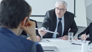 Zoom in of senior manager giving document to new employee at job interview and discussing something with young female colleague