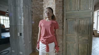 Zoom in of serious African woman with curly hair with sweater tied around waist standing against brick wall and looking into camera