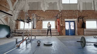 Zoom in of strong woman doing squats and throwing upwards medicine ball during cross training workout
