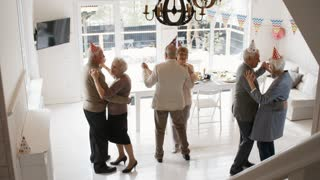 Zoom in of three senior couples wearing party hats and dancing in the living room while celebrating holiday together
