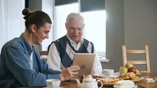 Zoom in shot of happy young man with ponytail showing tablet to grandfather with grey hair and teaching him to use it while having breakfast on sunny morning