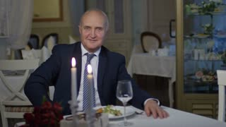 Zoom in shot of relaxed senior man in suit and tie sitting before table in restaurant and smiling while looking into camera