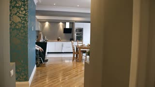 Zoom in shot of young female caregiver pushing elderly man on wheelchair in kitchen, then starting to prepare breakfast