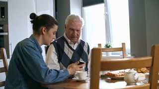 Zoom in shot of young man with ponytail helping senior man with grey hair and explaining how to use smartphone